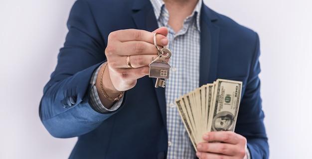 Mężczyzna trzymając się za ręce rachunki dolarów i klucz domu na białym tle. kup koncepcyjny lub kredyt na nieruchomość
