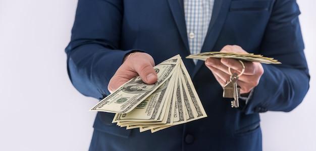 Mężczyzna trzymając się za ręce rachunki w dolarach amerykańskich i klucz domu na białym tle. zakup koncepcyjny lub pożyczka na zakup nieruchomości