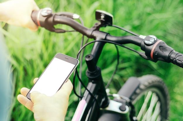 Mężczyzna trzymając się za ręce smartfona siedząc na rowerze górskim na leśnej drodze.