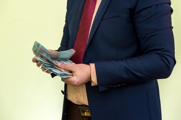 Mężczyzna trzymając się za ręce stos banknotów hrywny ukraińskiej na białym tle na zielono. hrywna nowe banknoty 1000, 500 i 200 uah. oszczędź koncepcję pieniędzy