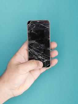 Mężczyzna, trzymając telefon z rozbitego ekranu