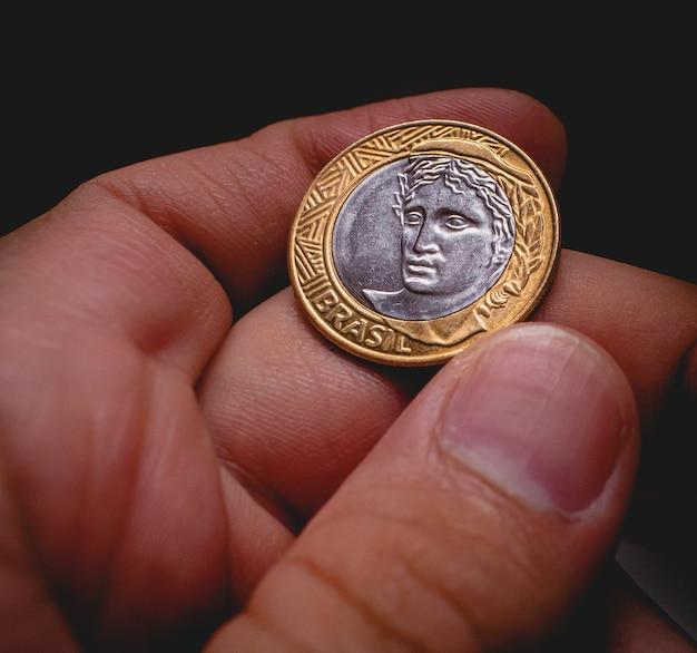 Mężczyzna trzymający 1 prawdziwą monetę brazylijskich pieniędzy