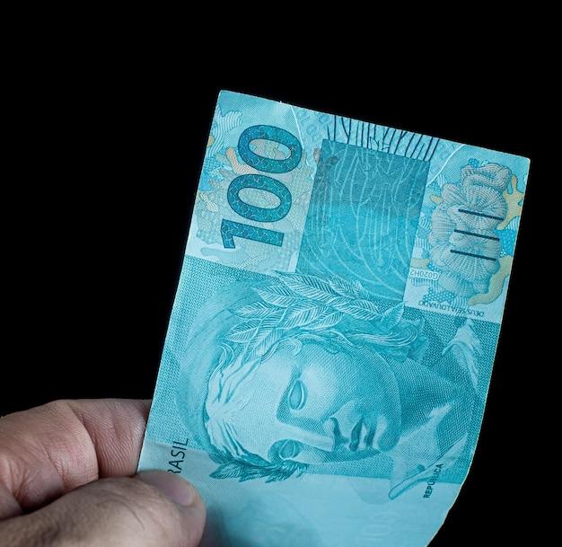 Mężczyzna trzymający 100 brazylijskich pieniędzy, które są brazylijskimi realami na czarnym tle