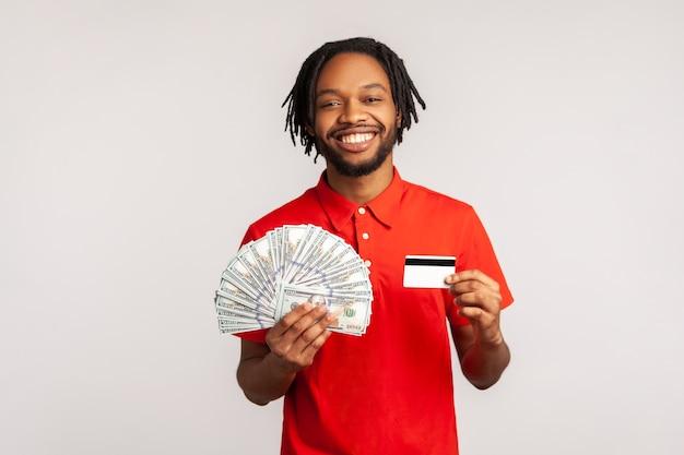 Mężczyzna trzymający banknoty dolarowe i kartę kredytową, patrzący na aparat z uśmiechem zębów, cieszący się