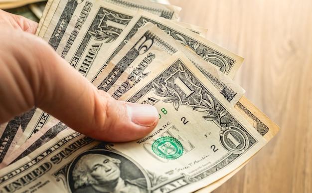 Mężczyzna trzymający banknoty dolarowe zdjęcie zbliżenie