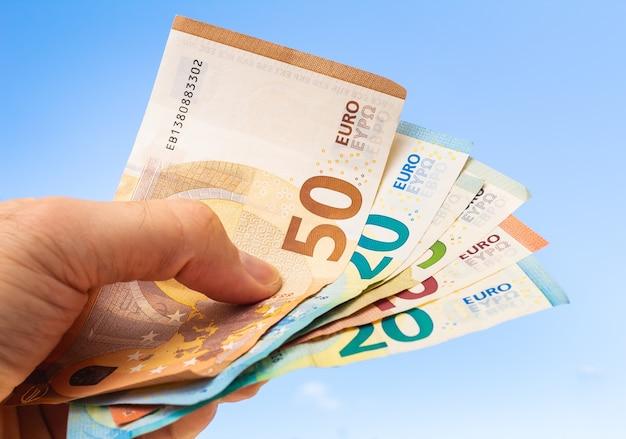 Mężczyzna trzymający banknoty euro na tle błękitnego nieba
