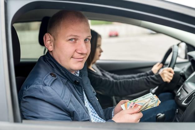 Mężczyzna trzymający banknoty euro siedzący w samochodzie