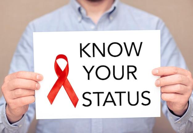 Mężczyzna trzymający białą kartkę z czerwoną wstążką na powierzchni i tekście - poznaj swój status. obraz koncepcyjny dotyczący hiv i pandemii aids na świecie