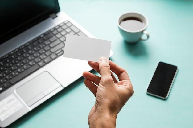 Mężczyzna trzymający białą wizytówkę na tle biurka