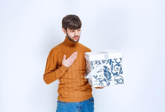 Mężczyzna trzymający białe pudełko z niebieskimi wzorami i wskazujący na siebie ze zdziwieniem.
