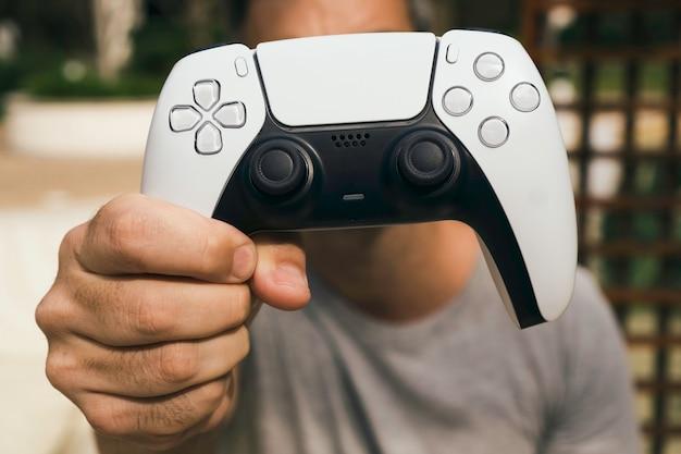 Mężczyzna trzymający biały kontroler do gier nowej generacji.