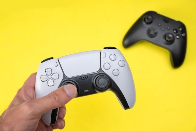 Mężczyzna trzymający biały kontroler gier nowej generacji i czarny z tyłu na żółtym tle