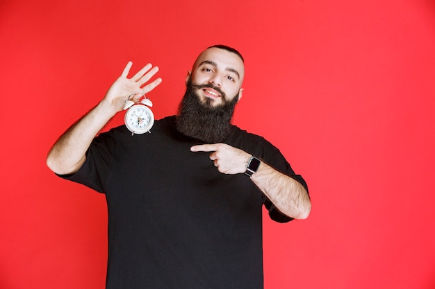 Mężczyzna trzymający brodę i promujący budzik jako produkt.