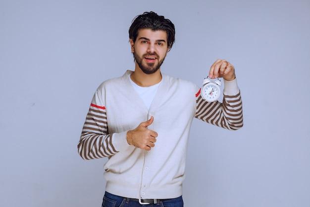 Mężczyzna Trzymający Budzik I Pokazujący, że Działa Dobrze I Cieszy. Darmowe Zdjęcia