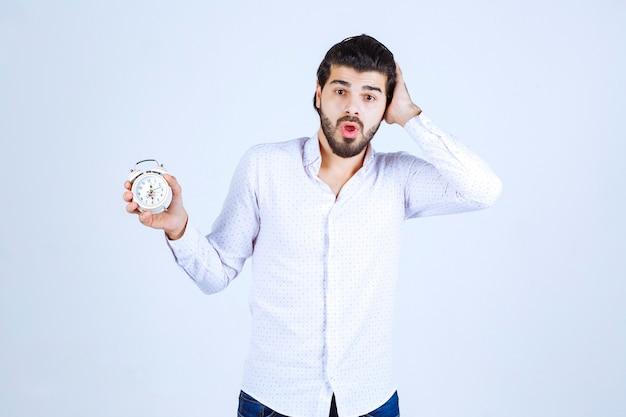 Mężczyzna trzymający budzik i zdezorientowany, ponieważ się spóźnia