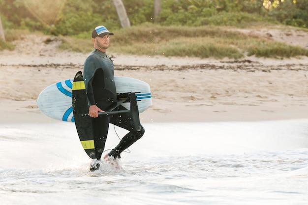 Mężczyzna trzymający deskę surfingową na zewnątrz