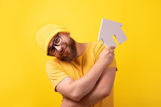 Mężczyzna trzymający dom reprezentujący własność domu i biznes nieruchomości, facet na żółtym tle