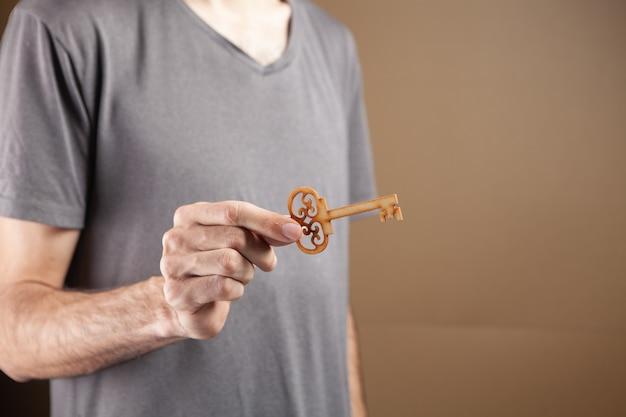 Mężczyzna trzymający drewniany klucz na brązowym tle