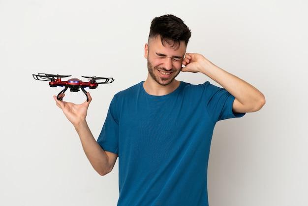Mężczyzna trzymający drona na białym tle sfrustrowany i zakrywający uszy
