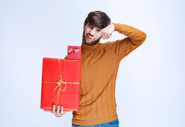 Mężczyzna trzymający duże i małe czerwone pudełka na prezenty i demonstrujący je.