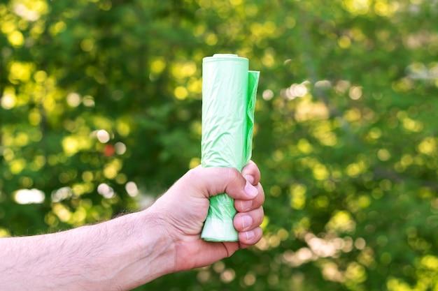 Mężczyzna trzymający eko plastikową zieloną torbę na śmieci w rolce na zewnątrz