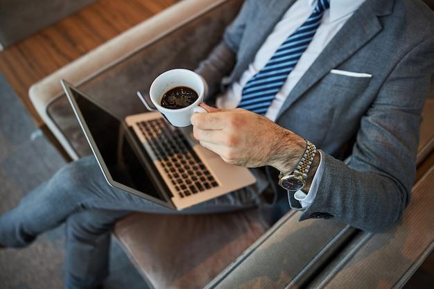 Mężczyzna trzymający filiżankę espresso nad laptopem