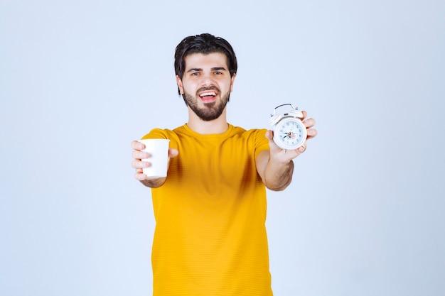 Mężczyzna trzymający filiżankę kawy i budzik wskazujący na poranną rutynę.