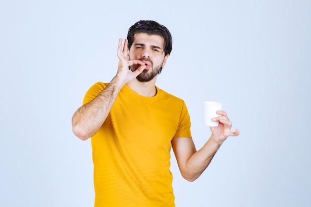 Mężczyzna trzymający filiżankę kawy i cieszący się smakiem.