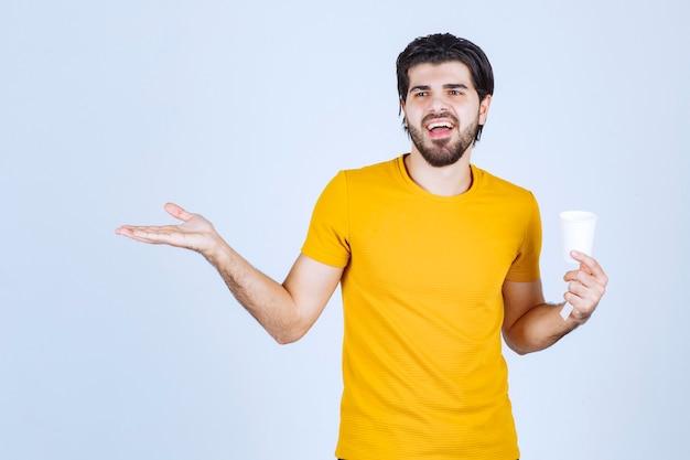 Mężczyzna trzymający filiżankę kawy i dając prezentację za pomocą otwartej dłoni.
