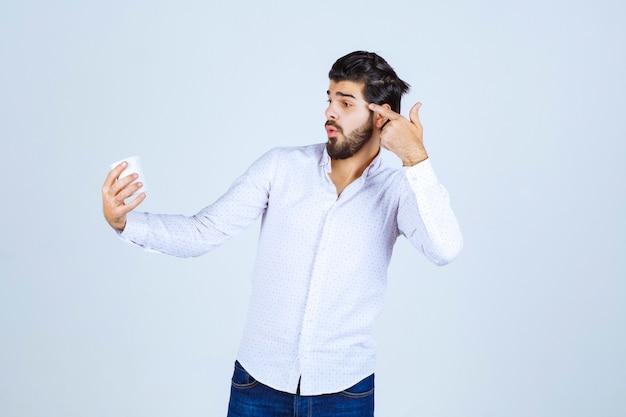 Mężczyzna trzymający filiżankę kawy i myślący