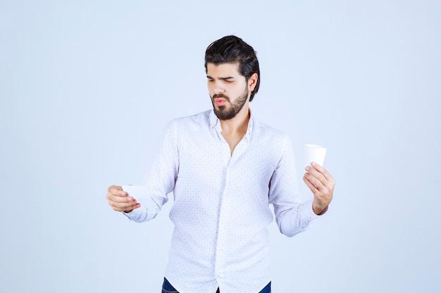 Mężczyzna trzymający filiżankę kawy i sprawdzający dane na wizytówce