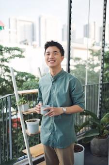 Mężczyzna trzymający filiżankę kawy i uśmiechający się na balkonie