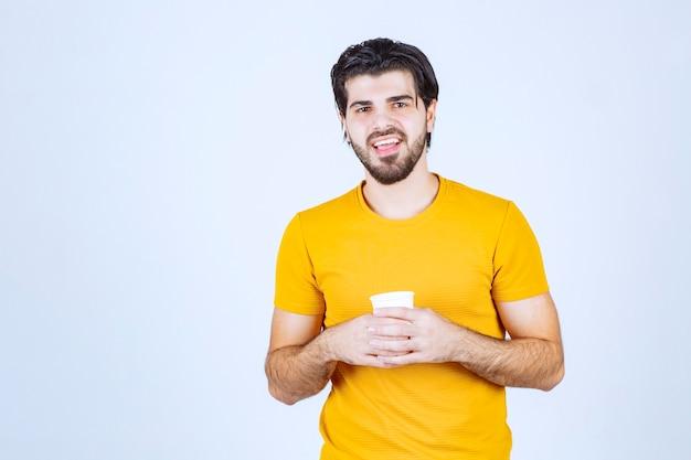 Mężczyzna trzymający filiżankę kawy jednorazowego użytku między rękami.