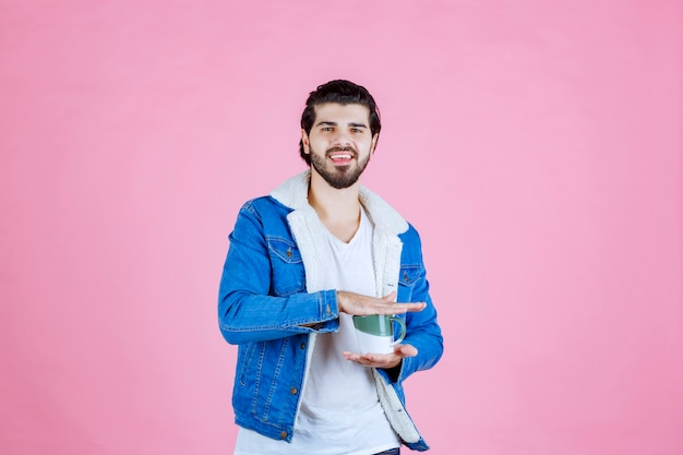 Mężczyzna trzymający filiżankę kawy w dwóch rękach