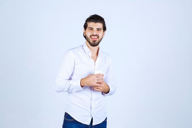 Mężczyzna trzymający filiżankę napoju i odczuwający satysfakcję