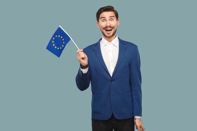 Mężczyzna trzymający flagę unii europejskiej i patrzący na kamerę ze zdziwioną twarzą