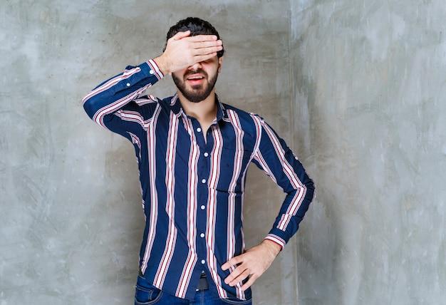 Mężczyzna trzymający głowę rękami, bo boli go głowa.