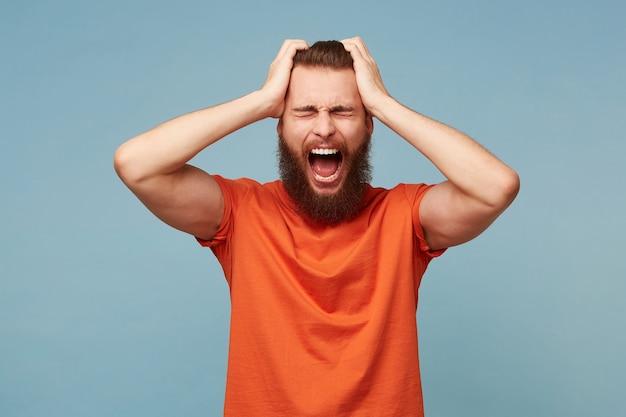 Mężczyzna trzymający głowę rękami krzyczy głośno, wyraz twarzy złości, odizolowany na niebiesko.