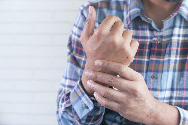 Mężczyzna trzymający go za nadgarstek i cierpiący ból w ręku z miejsca na kopię
