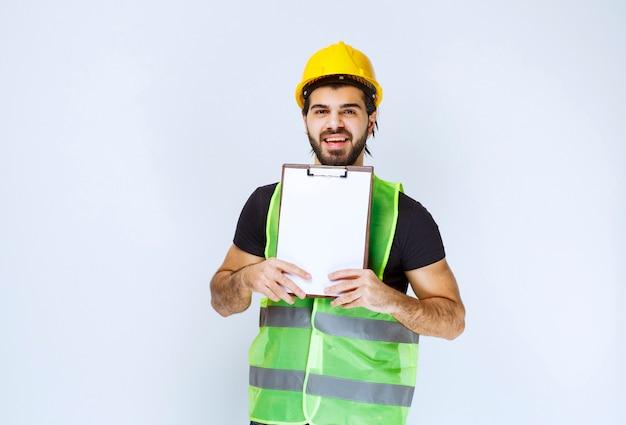 Mężczyzna trzymający i demonstrujący ostateczną wersję projektu budowlanego.