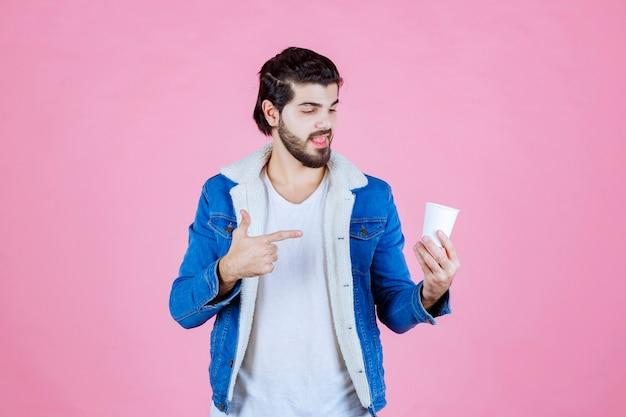 Mężczyzna trzymający i prezentujący nową jednorazową filiżankę kawy