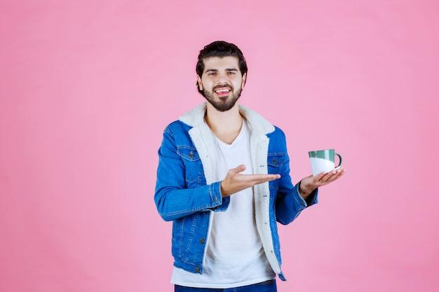 Mężczyzna trzymający i promujący filiżankę kawy lub kawę