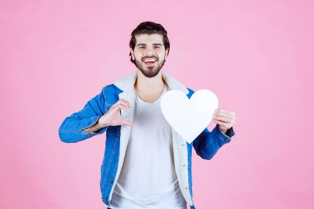 Mężczyzna trzymający i przedstawiający pustą postać serca z uśmiechem