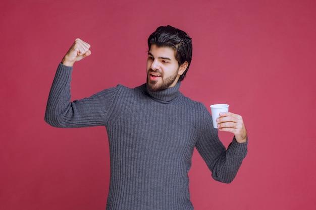Mężczyzna trzymający jednorazową filiżankę kawy, czujący siłę i energię.