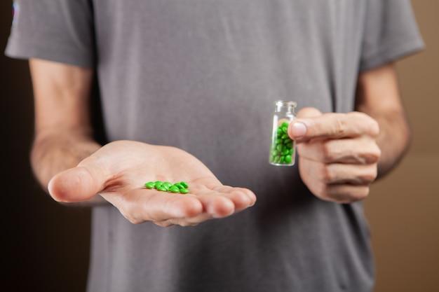 Mężczyzna trzymający kapsułkę z tabletkami na brązowym tle