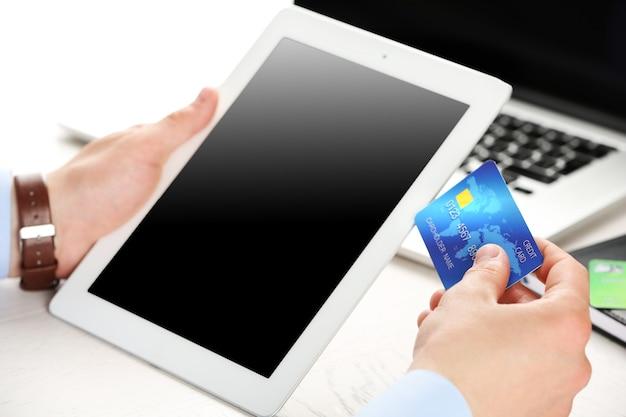 Mężczyzna trzymający kartę kredytową i tablet na powierzchni w miejscu pracy