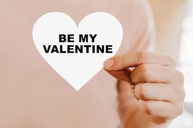 Mężczyzna trzymający kartę miłości w kształcie serca z być moją walentynką