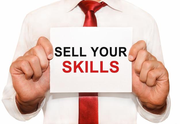 Mężczyzna trzymający kartę z tekstem sell your skills