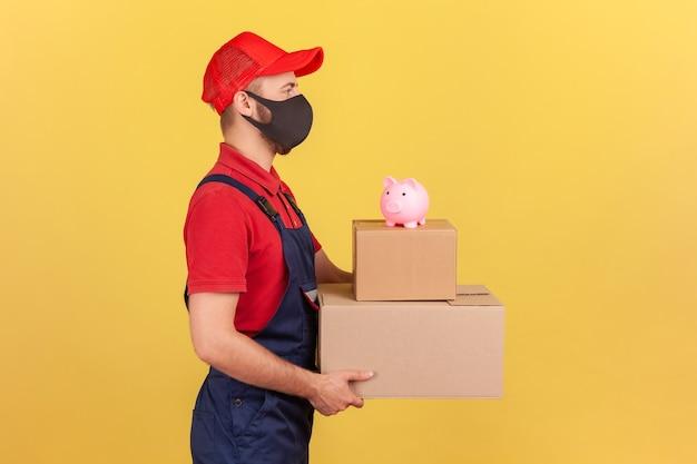 Mężczyzna trzymający kartonowe paczki ze skarbonką na górze oszczędzać pieniądze zamawiając reklamę dostawy