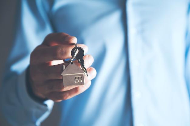 Mężczyzna trzymający klucz do domu na pęku kluczy w kształcie domu